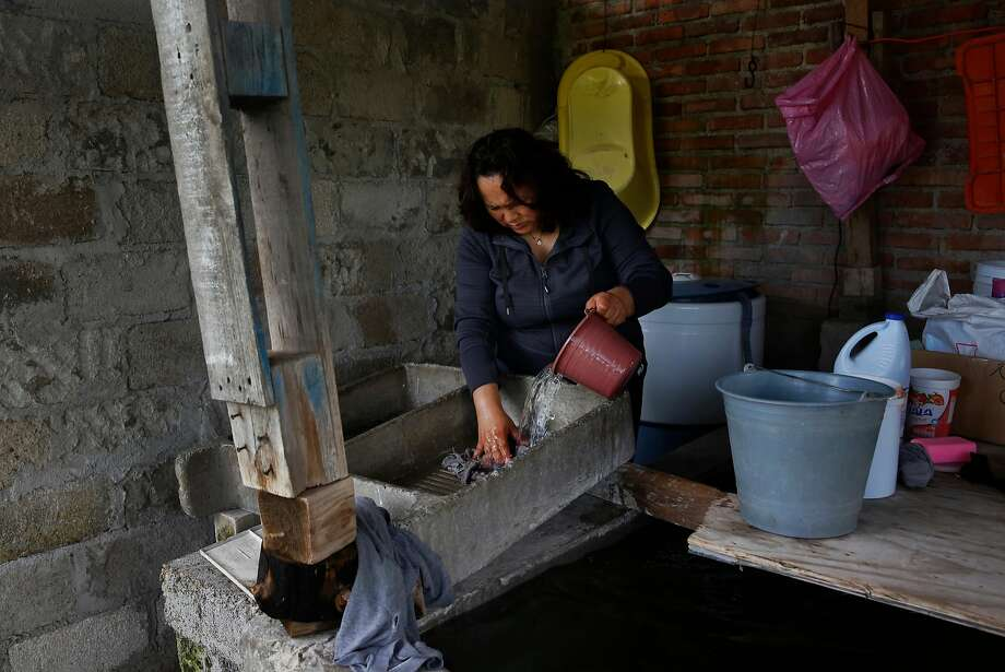 Maria Mendoza-Sanchez washes a rag in a concrete washbasin behind her mother's home. Photo: Leah Millis, The Chronicle