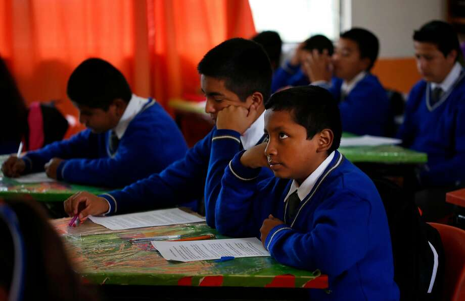 Jesus Sanchez, 12 (right), listens to the teacher read literature with his cousin Francisco Mejia, 13, at school in Mexico. School has been difficult for Jesus because Spanish is not his first language, and the teacher is much more strict than U.S. teachers are. Photo: Leah Millis, The Chronicle