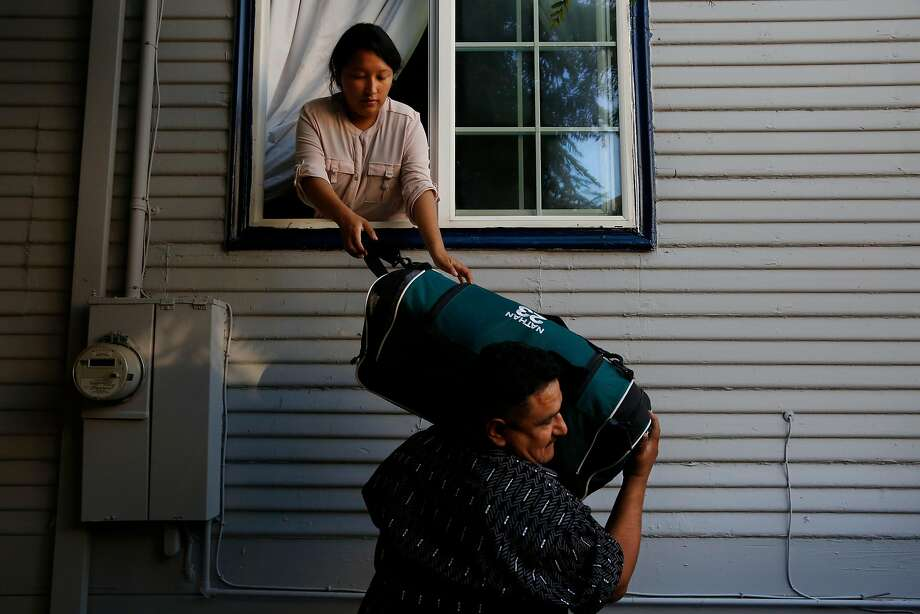 Melin Sanchez, 21, helps her father Eusebio pack the car by handing him luggage through the window August 16, 2017 in their home in Oakland, Calif. The family's application for a stay was denied. Photo: Leah Millis, The Chronicle