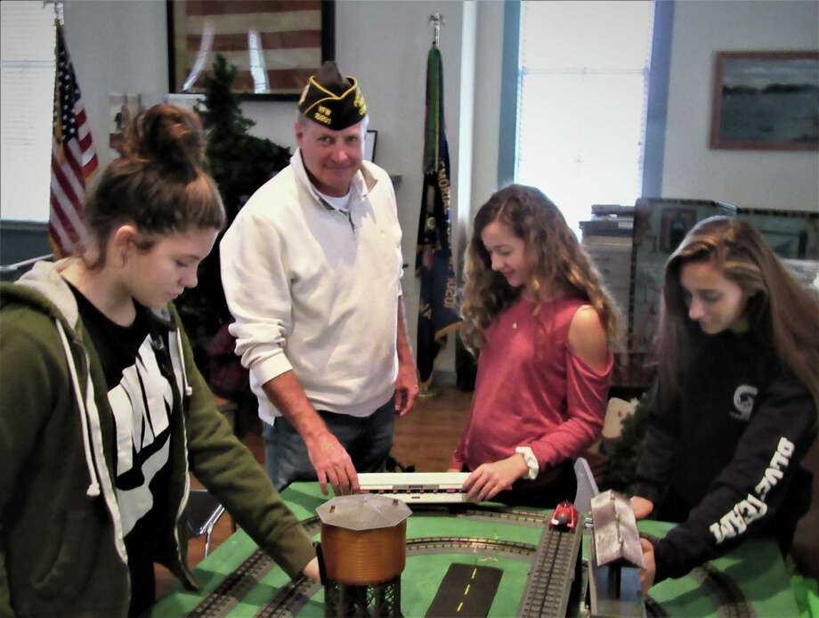 Joseph Beal, commander of the Brookfield VFW Post, center, with Brookfield High School students Mia Ballard, Emma Beal and Lexi Nunnally set up a model train display for the upcoming veterans family holiday open house in Brookfield. Photo: / Contributed Photo