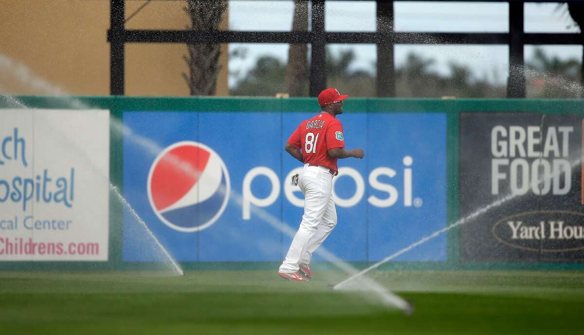 St. Louis Cardinals left fielder Anthony Garcia jogs away after automatic sprinklers came on unexpectedly during the sixth inning of an exhibition spring training baseball game against the New York Mets Monday, March 7, 2016, in Jupiter, Fla. (AP Photo/Jeff Roberson)
