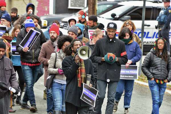 Dahmeek McDonald's uncle, identified only as Messiah,center, leads a rally to draw attention to the police killing of Edson Thevenin and shooting of Dahmeek McDonald and to call for the use of a civilian review board Saturday Nov. 18, 2017 in Troy, NY.