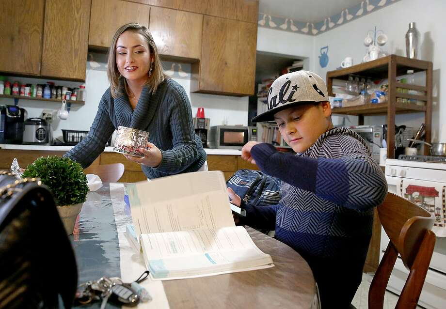 Melody Nichols, who underwent sudden surgery for acute appendicitis, gets settled while her 12-year-old son Angel starts on his math homework after school in San Francisco. Season of Sharing paid Nichols' July rent. Photo: Liz Hafalia, The Chronicle