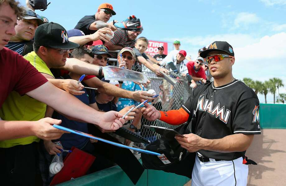 Miami Marlins right fielder Giancarlo Stanton signing autographs during the fifth inning a spring training baseball game against the Washington Nationals Friday, March 4, 2016, at Roger Dean Stadium in Jupiter, Fla. (David Santiago/El Nuevo Herald via AP)  MAGS OUT; MANDATORY CREDIT Photo: David Santiago, AP