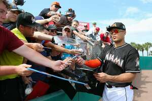 Miami Marlins right fielder Giancarlo Stanton signing autographs during the fifth inning a spring training baseball game against the Washington Nationals Friday, March 4, 2016, at Roger Dean Stadium in Jupiter, Fla. (David Santiago/El Nuevo Herald via AP)  MAGS OUT; MANDATORY CREDIT