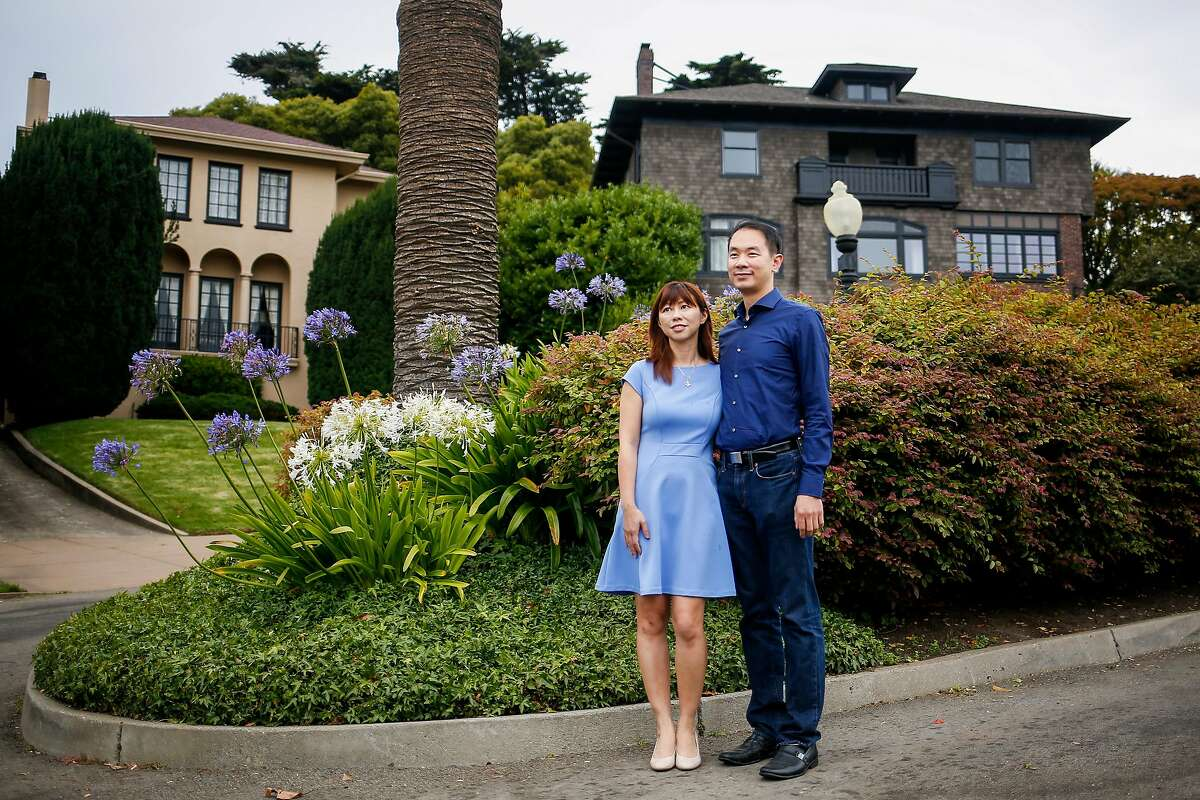 Hiuyan Tina Lam, left, and her husband Michael Cheng, right, stand for a portrait on Presidio Terrace, a street she bought in auction from the City of San Francisco, that is inside the exclusive gated community of Presidio Terrace in San Francisco on Friday, August 4, 2017.