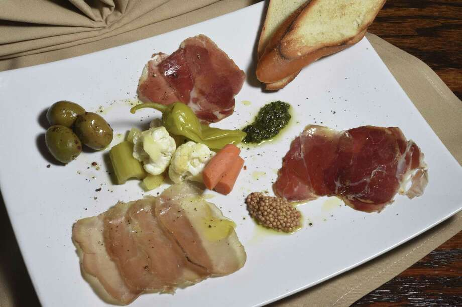 Rossini Italian Bistro served a salumi platter, which includes house-cured lonza, bresaola and copper, almond pesto, marinated olives and house giardinara. Photo: Billy Calzada /San Antonio Express-News / San Antonio Express-News