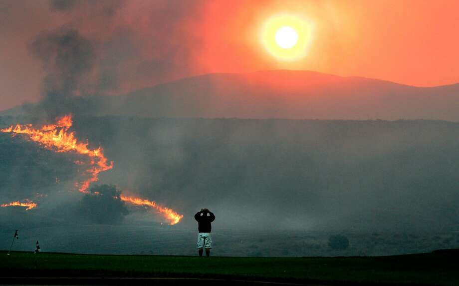 Flames advance near Chula Vista in San Diego County during a devastating series of wildfires in 2007. San Diego Gas & Electric Co., whose equipment helped spark the wind-driven fires, wants its customers to pay some of the costs of lawsuits that followed the flames. Photo: Brian Vander Brug, AP