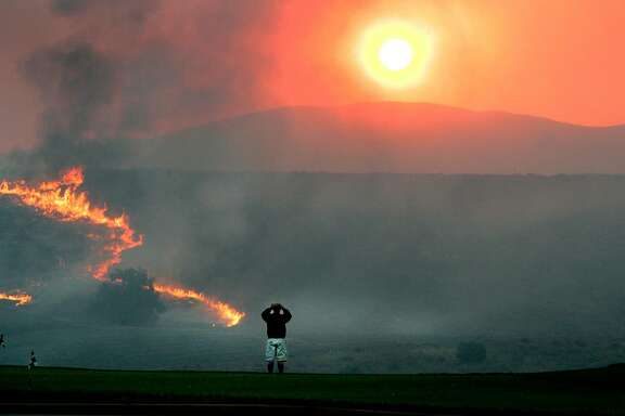 Chula Vista resident John Mercado watches the sunrise as flames lick a hillside above Salt Creek Golf Club in the San Diego County town of Chula Vista, Calif. Tuesday morning Oct. 23 2007. (AP Photo/ Los Angeles Times, Brian Vander Brug)*** MANDATORY CREDIT. NO SALES, NO FOREIGN, NO MAGS, NO TELEVISION, INTERNET - AP Members Only. LOS ANGELES DAILY NEWS OUT, ORANGE COUNTY REGISTER OUT, VENTURA COUNTY STAR OUT, INLAND VALLEY DAILY BULLETIN OUT, SAN BERNARDINO SUN OUT, LA OPINION OUT.Mobile phones out. ***
