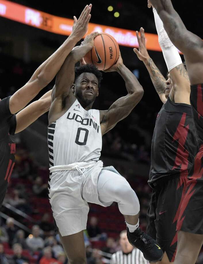 UConn guard Antwoine Anderson feels the pressure and is fouled but managed to score and convert on the three-point play during the second half against Arkansas on Sunday. Photo: Patrick Raycraft / TNS / Hartford Courant