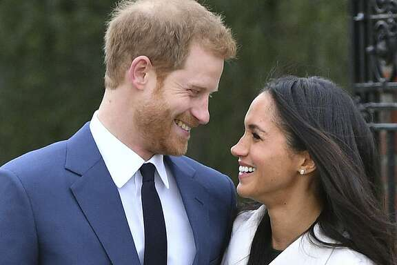 Britain's Prince Harry and Meghan Markle smile as they pose for the media in the grounds of Kensington Palace in London, Monday Nov. 27, 2017. It was announced Monday that Prince Harry, fifth in line for the British throne, will marry American actress Meghan Markle in the spring, confirming months of rumors. (Dominic Lipinski/PA via AP)