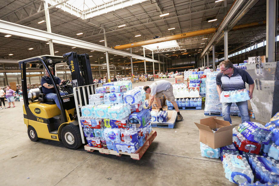 Moises Vaglienty, of National Oilwell Varco, uses a forklift to move pallets of donated water bottles on Friday, Sept. 1, 2017, at Falcon Steel America's warehouse in Conroe. National Oilwell Varco donated two of its forklifts to help organize supplies for Montgomery County residents affected by Tropical Storm Harvey. Photo: Michael Minasi, Staff Photographer / Internal