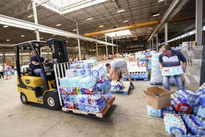Moises Vaglienty, of National Oilwell Varco, uses a forklift to move pallets of donated water bottles on Friday, Sept. 1, 2017, at Falcon Steel America's warehouse in Conroe. National Oilwell Varco donated two of its forklifts to help organize supplies for Montgomery County residents affected by Tropical Storm Harvey.
