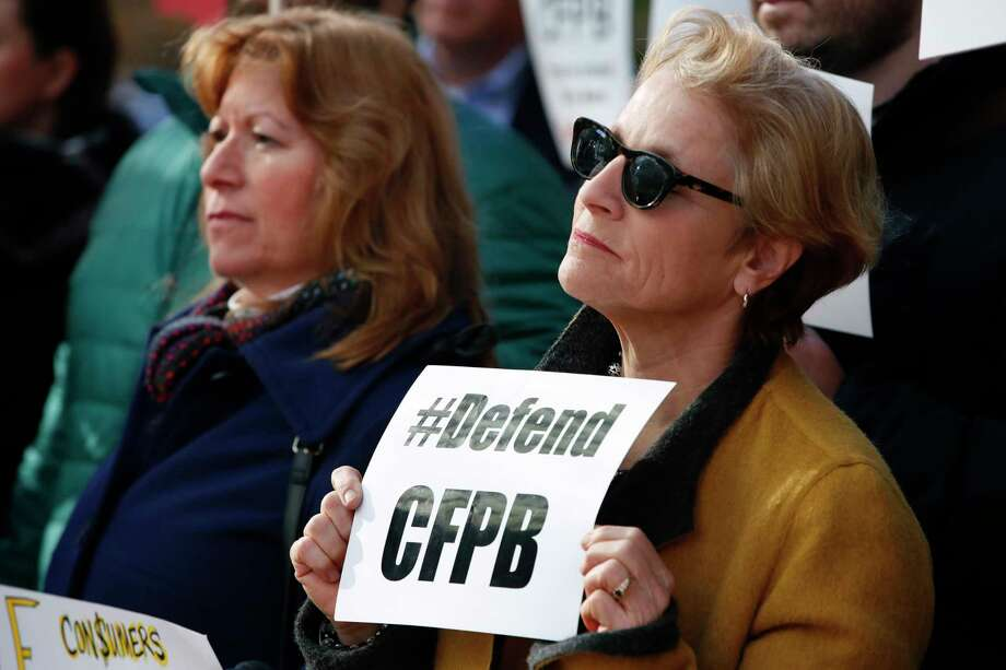 """Sally Greenberg, with the National Consumers League, right, holds a sign that says """"Defend CFPB"""" outside of the Consumer Financial Protection Bureau in Washington, Monday, Nov. 27, 2017, during a news conference with consumer groups that oppose Mick Mulvaney being named acting director for the bureau. (AP Photo/Jacquelyn Martin) Photo: Jacquelyn Martin, STF / Copyright 2017 The Associated Press. All rights reserved."""