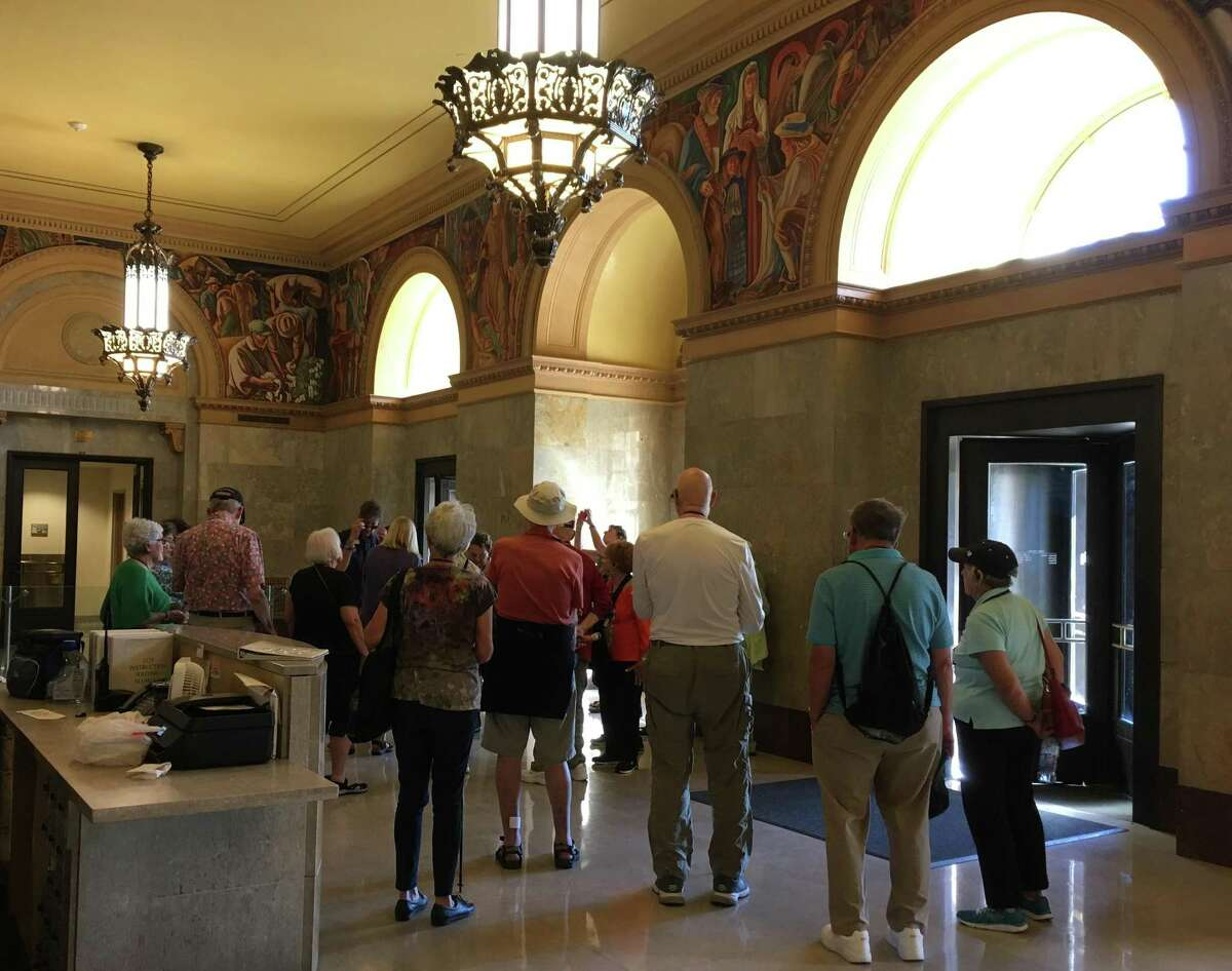 """A group of tourists from Austin-based, """"Road Scholar,"""" view the murals on a recent weekday afternoon in the Post Office on the Hipolito F. Garcia's Federal Building's main floor."""