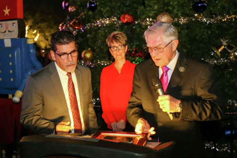 Mayor Toby Powell, right, presents a proclamation to Conroe City Administrator Paul Virgadamo, left, and his wife Stephanie, center, during the Tree Lighting Ceremony on Tuesday at Heritage Place in downtown Conroe. The ceremony was followed by an expanded evening of Christmas festivities in the new Christmas on Main Street event. Photo: Michael Minasi, Staff Photographer / © 2017 Houston Chronicle