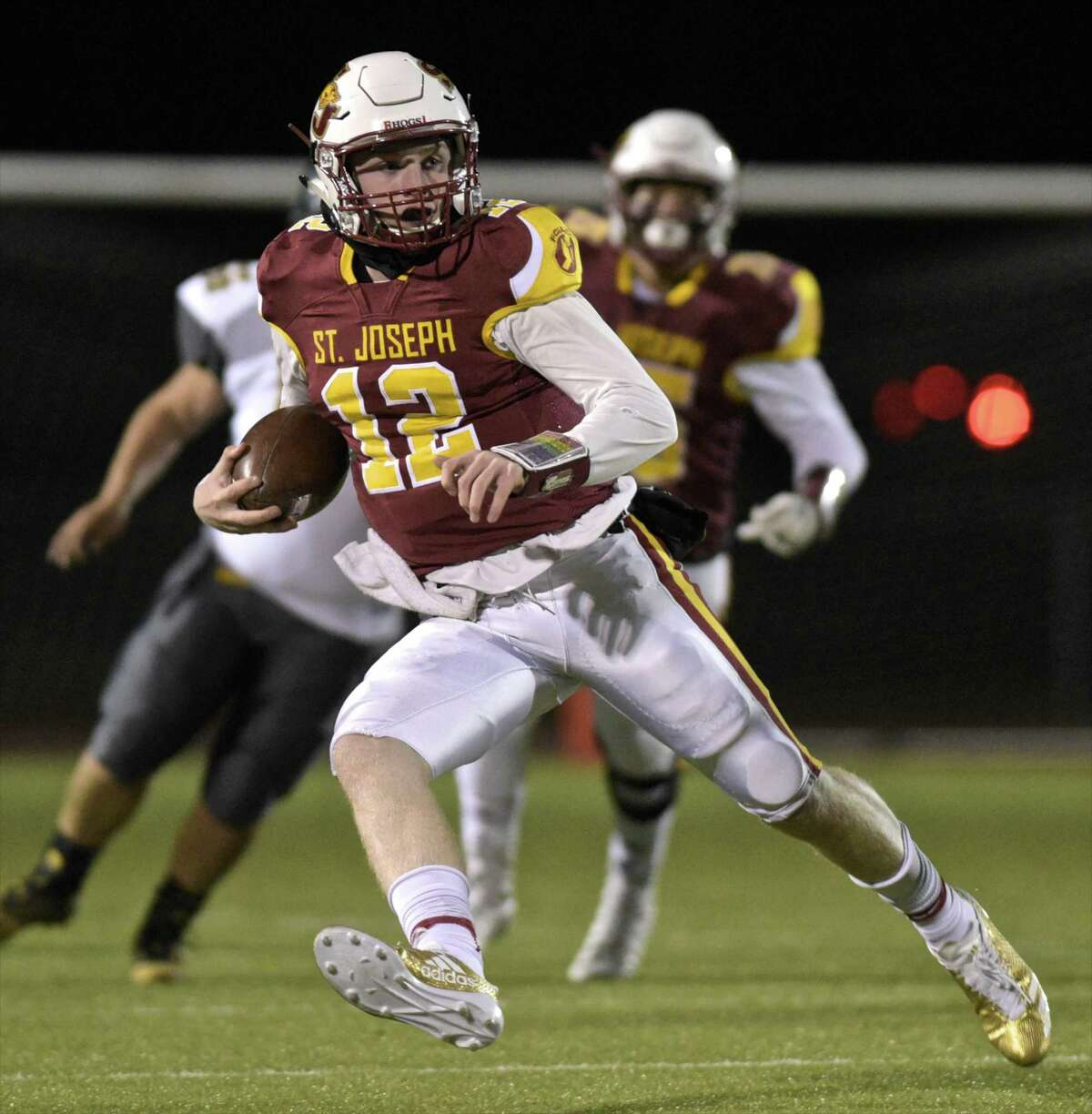 St Joe quarterback David Summers (12) is chased out of the backfield in the Class S football playoff game between O'Brien Tech and St.Joseph high schools on Tuesday night, November 28, 2017, at Trumbull High School, in Trumbull, Conn.
