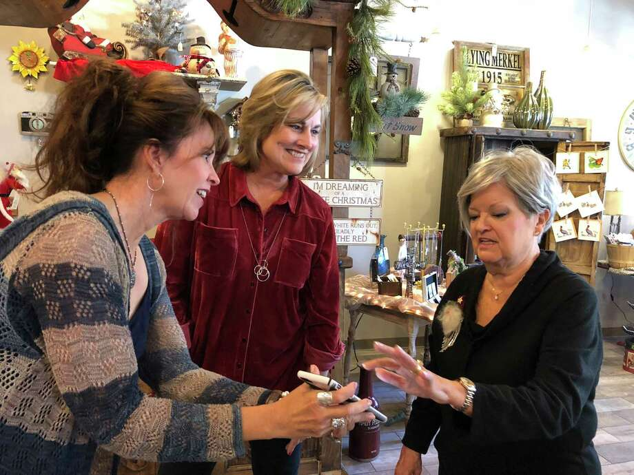 Gnome Sweet Gnome co-owner Mary Beth Baker, left, shows artist Pat Wallace, right, a picture taken several years ago of Baker's niece with one of Wallace's life-size Santa sculptures. Business co-owner Sally Kelly is pictured center. Photo: Julie Silva
