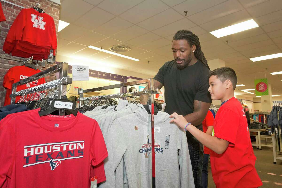 IMAGE DISTRIBUTED FOR JCPENNEY - Houston Texan Jadeveon Clowney takes kids from the YMCA of Greater Houston shopping at JCPenney Meyerland Plaza as part of the retailer's annual holiday giving sprees, where kids select holiday gifts for their family and friends on Tuesday, Nov. 28, 2017, in Houston. (Anthony Rathbun/AP Images for JCPenney)