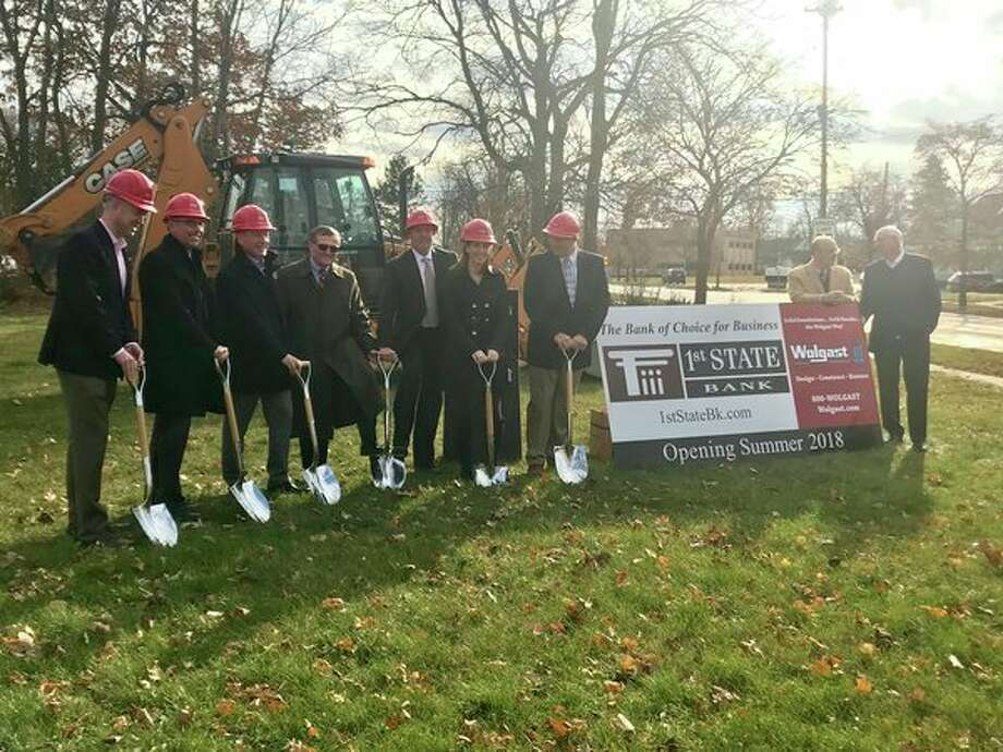 1st State Bank board members poseon Tuesday, Nov. 28 at the site of a future branch located at 400 Ashman Street near downtown Midland. (Kate Carlson/kcarlson@mdn.net)