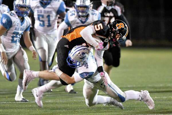 West Haven's Zach Conlan (4) tackles Shelton's Jack Carr during the West Haven and Shelton Class LL state football quarterfinals at Shelton, November 28, 2017.