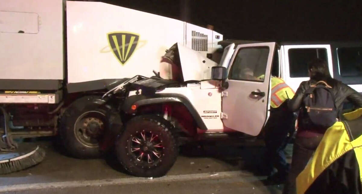 A woman crashes her Jeep Wrangler into the back of a street sweeper early Wednesday morning. A combination of thick fog and dust reportedly contributed to the crash, according to authorities.