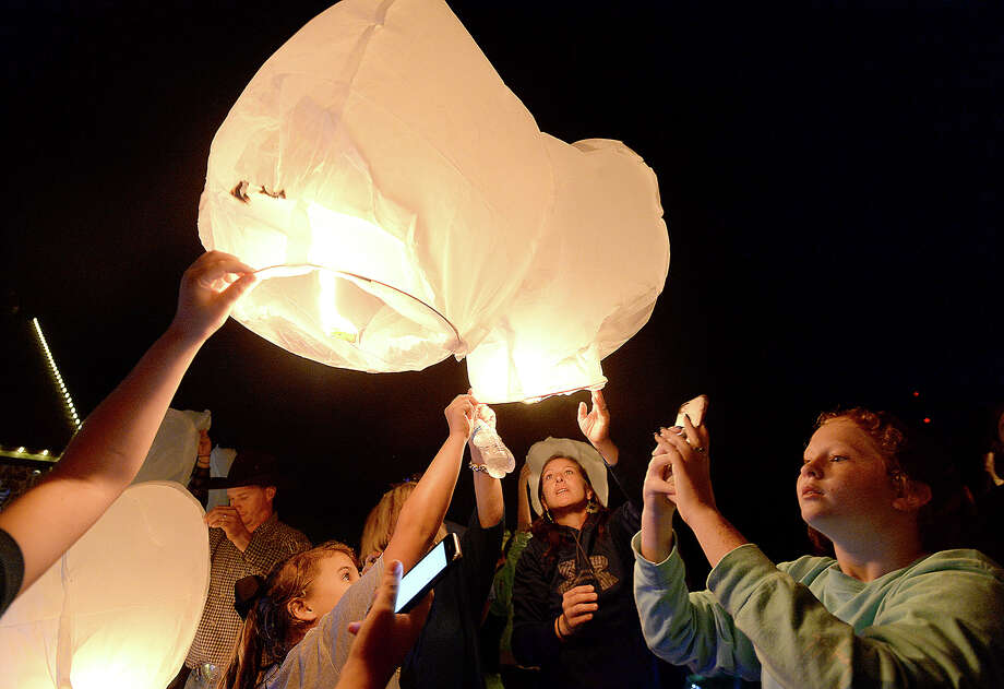 Family, friends, and members of the Hamshire community ligth and release lanterns into thesky as they gather to decorate the home of Shane, Aimee, and Trevor Chesson Tuesday. Ten-year-old Trevor was killed in an ATV accident at his family's home on Monday. The Chesson's, who were no longer living at the house after it was damaged by Harvey's flooding, returned Monday to begin decorating for Christmas at Trevor's request. In his memory, the community came together to complete his wish, spreading out through the grounds and around the home, putting up lights, trees, and other holiday decor. Shane and Aimee Chesson arrived shortly after sunset, when the group collectively lit up the display upon their arrival. The Chesson's then gathered in a circle, Shane thanking the group for their support and asking for continued strength in the days to come, before a local pastor offered a prayer. Photo taken Tuesday, November 28, 2017 Kim Brent/The Enterprise Photo: Kim Brent / BEN