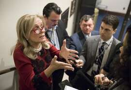 Rep. Debbie Dingell, D-Mich., left, responds to reporters after members of the House Democratic Caucus met on Capitol Hill in the wake of reports of sexual misconduct by Rep. John Conyers, D-Mich., the longest-serving member of the House, in Washington, Wednesday, Nov. 29, 2017. Conyers returned to his home in Detroit, Tuesday. (AP Photo/J. Scott Applewhite)