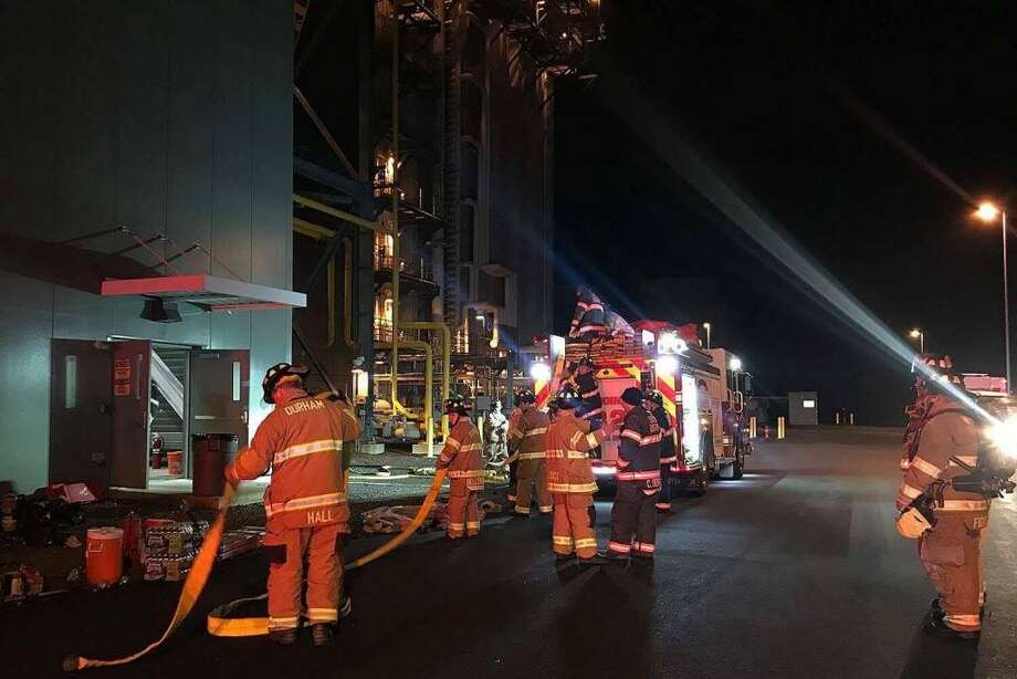 Haddam Volunteer Fire Company crews, who provided mutual aid to a small fire Tuesday night at the Kleen Energy power plant in Middletown, pack up hoses after the blaze was put out three hours later. Photo: Olivia Drake Photo