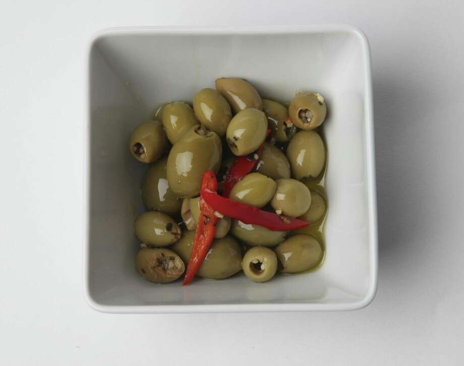 Pitted green olives are marinated in olive oil with minced garlic and a red chile. Photo: Juanito M. Garza /San Antonio Express-News / San Antonio Express-News