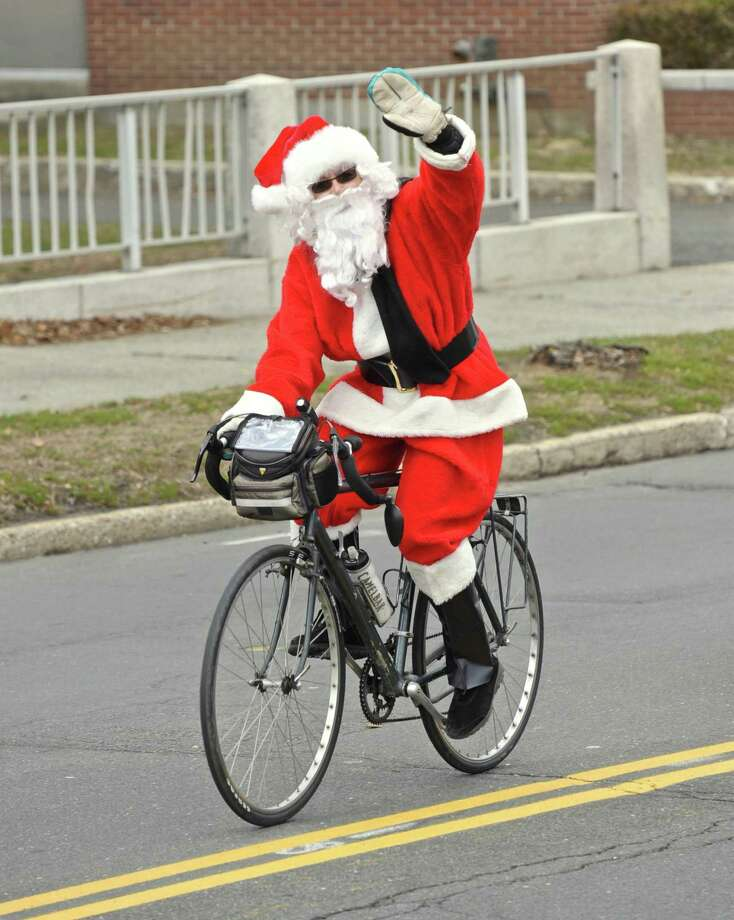 Elaine Daubner, of New Milford, waves to passing motorist as the 3rd Annual Santa Ride heads up West Street in Danbury. The 13 mile route took riders through Danbury and Bethel with multiple stops to refuel along the way. Saturday morning, December 3, 2016, in Danbury, Conn. Photo: H John Voorhees III / Hearst Connecticut Media / The News-Times