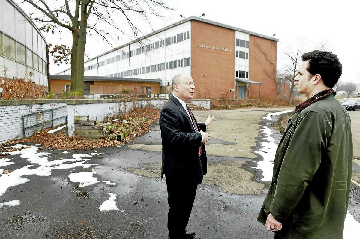 (Peter Hvizdak - New Haven Register) ¬ Dale Kroop, Hamden Director of Economic and Community Development, left, and State Representative Michael C. D'Agostino, D-71 of Hamden discuss the $600,00state grant for the abatement and demolition of a portion of the Michael J. Whalen school building while standing at that was the former Hamden Middle School building on 560 Newhall Street inHamden to prepare the site for a private mixed-use redevelopment Thursday, February 23, 2017