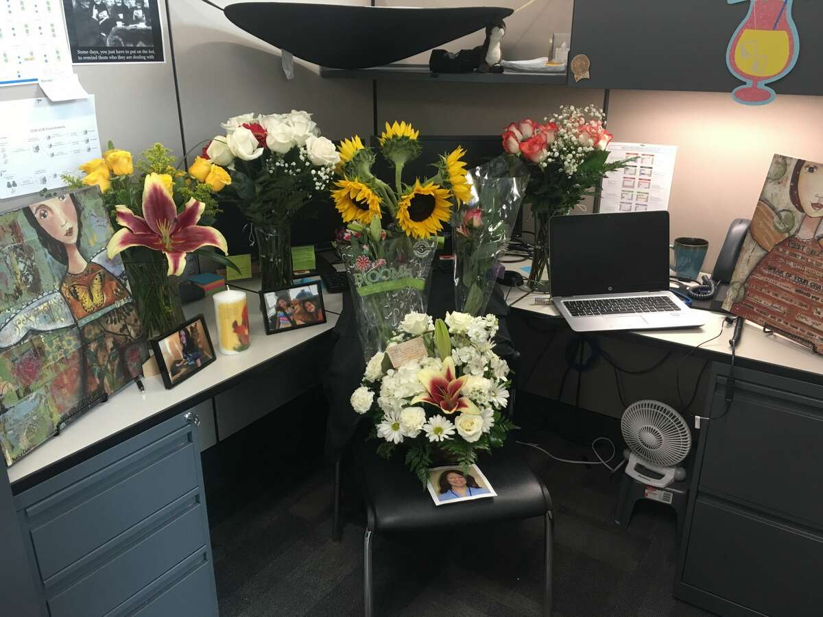 A small memorial with fresh flowers and framed pictures sits in a cubicle at WellMed Medical Management's office in San Antonio. The cubicle belonged to 46-year-old Jennifer Smith until Monday, when her husband, 54-year-old William Scott Smith, allegedly fatally shot her at their North Side home before turning the gun on himself.