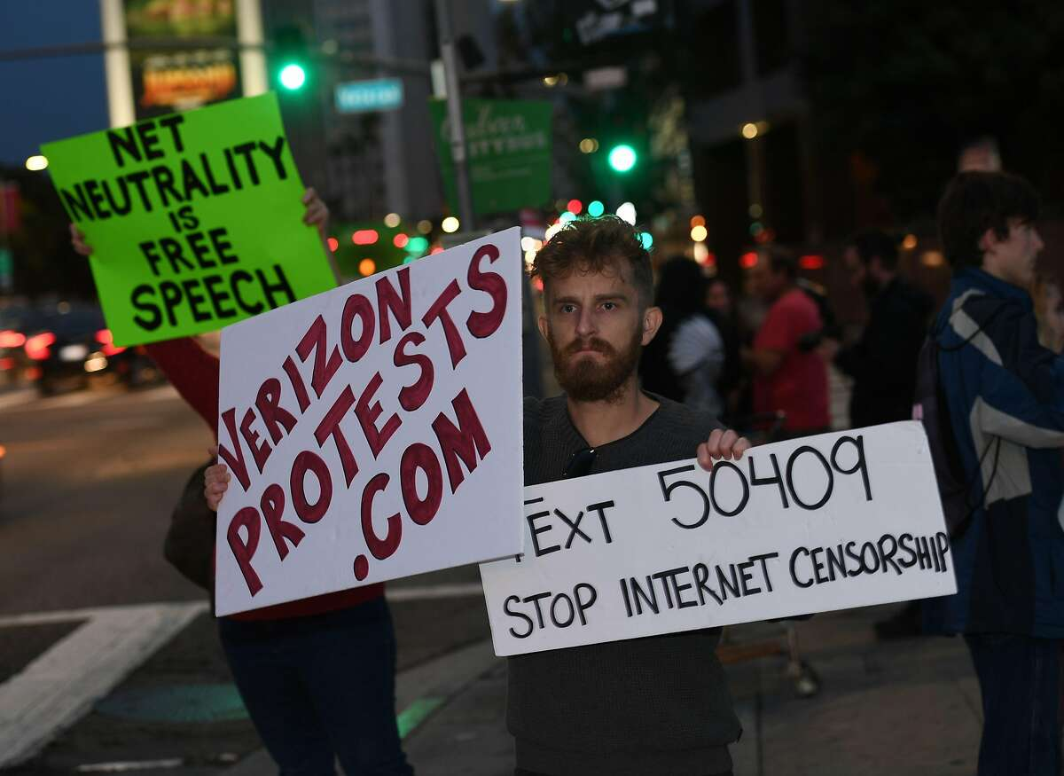 """People protest during a rally to 'Protect Net Neutrality' as they voice their opposition to the impending FCC vote, outside the Federal Building in Los Angeles, California on November 28, 2017. Organizers say """"that a ruling in favor of repealing the 2015 rules could result in internet service providers prioritizing connection speeds to certain sites, such as advertisers, with access to certain websites being restricted at the service providers discretion and the opportunity to raise fees for access that otherwise is free"""". / AFP PHOTO / Mark RALSTONMARK RALSTON/AFP/Getty Images"""