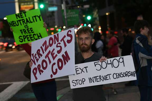 "People protest during a rally to 'Protect Net Neutrality' as they voice their opposition to the impending FCC vote, outside the Federal Building in Los Angeles, California on November 28, 2017.   Organizers say ""that a ruling in favor of repealing the 2015 rules could result in internet service providers prioritizing connection speeds to certain sites, such as advertisers, with access to certain websites being restricted at the service providers discretion and the opportunity to raise fees for access that otherwise is free"". / AFP PHOTO / Mark RALSTONMARK RALSTON/AFP/Getty Images"