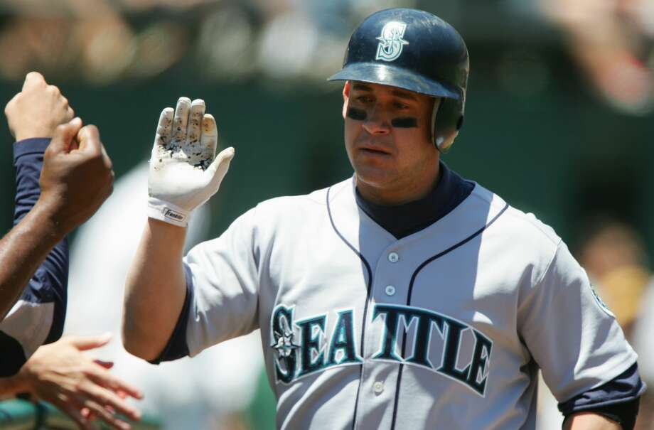 Bret Boone of the Seattle Mariners high fives teammates during an MLB game against the Oakland Athletics at McAfee Coliseum on June 30, 2005 in Oakland, California. Photo: Jed Jacobsohn/Getty Images