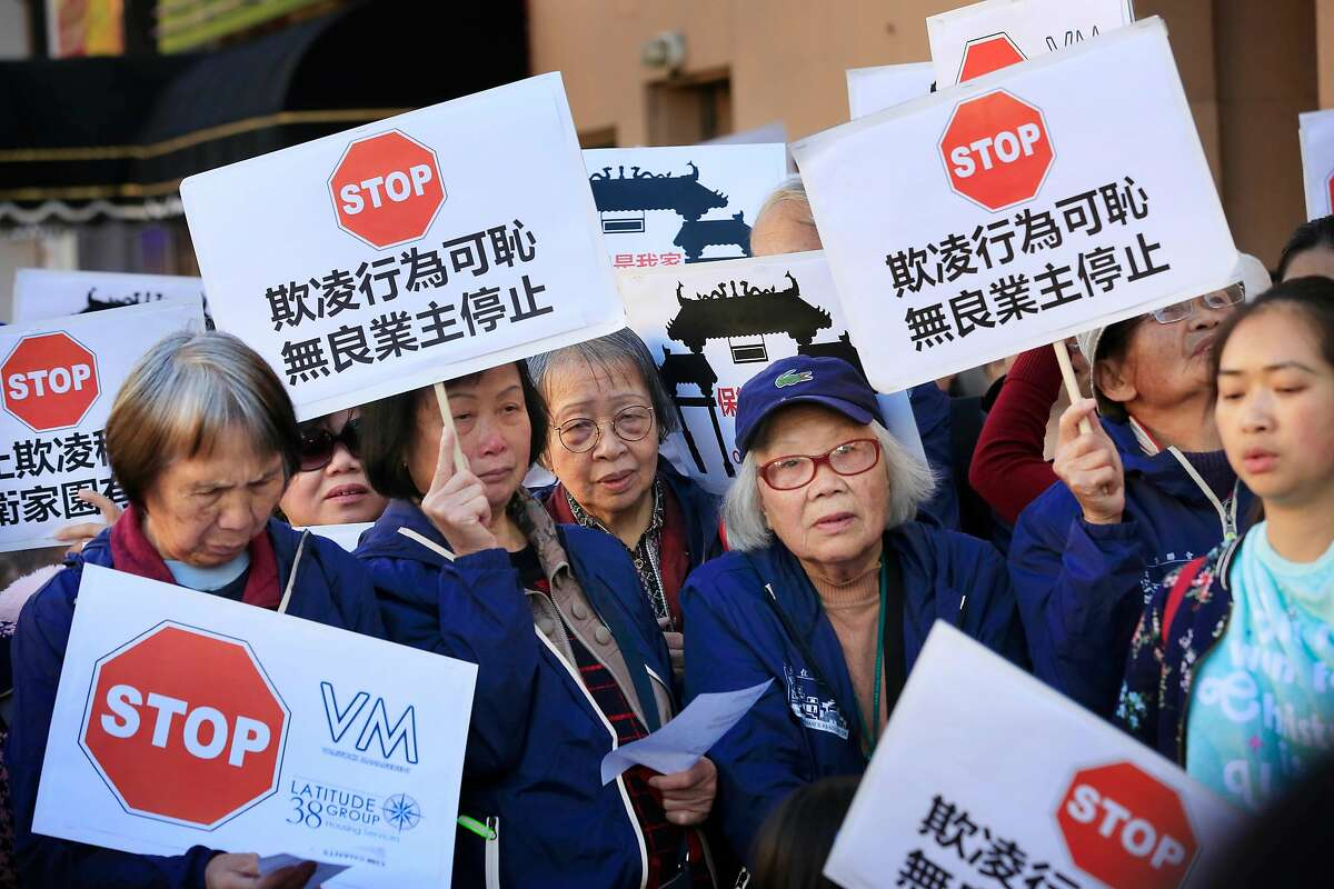 People listen to speakers at a rally on Wednesday, November 29, 2017 in San Francisco, Calif. Today a coalition of tenant, civl rights, and community organizations announced a campaign to protect tenants against intimidation, evictions, and increasing rents in Chinatown.