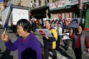 People rally along Stockton Street on Wednesday, November 29, 2017 in San Francisco, Calif.  Today a coalition of tenant, civl rights, and community organizations announced a campaign to protect tenants against intimidation, evictions, and increasing rents in Chinatown.