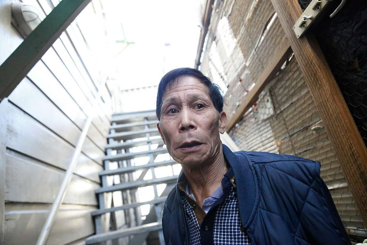 Tenant Huang Wong stands on a exterior stairwell landing at 1350 Stockton where he says tenants used to hang clothes to dry and no longer can under the rules of new managers on Wednesday, November 29, 2017 in San Francisco, Calif.