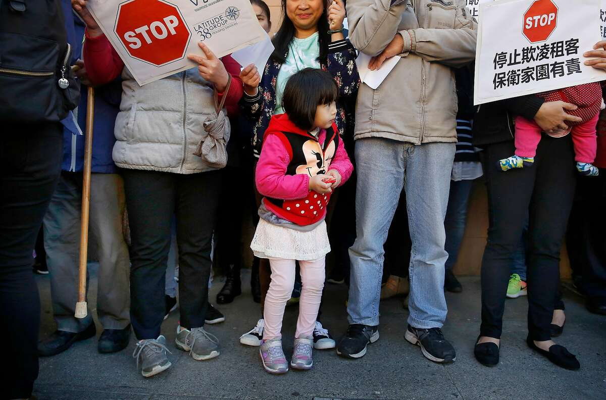 Shirley Chen, 4, stands with her mother as they attend a rally outside 1350 Stockton on Wednesday, November 29, 2017 in San Francisco, Calif. Today a coalition of tenant, civl rights, and community organizations announced a campaign to protect tenants against intimidation, evictions, and increasing rents in Chinatown.
