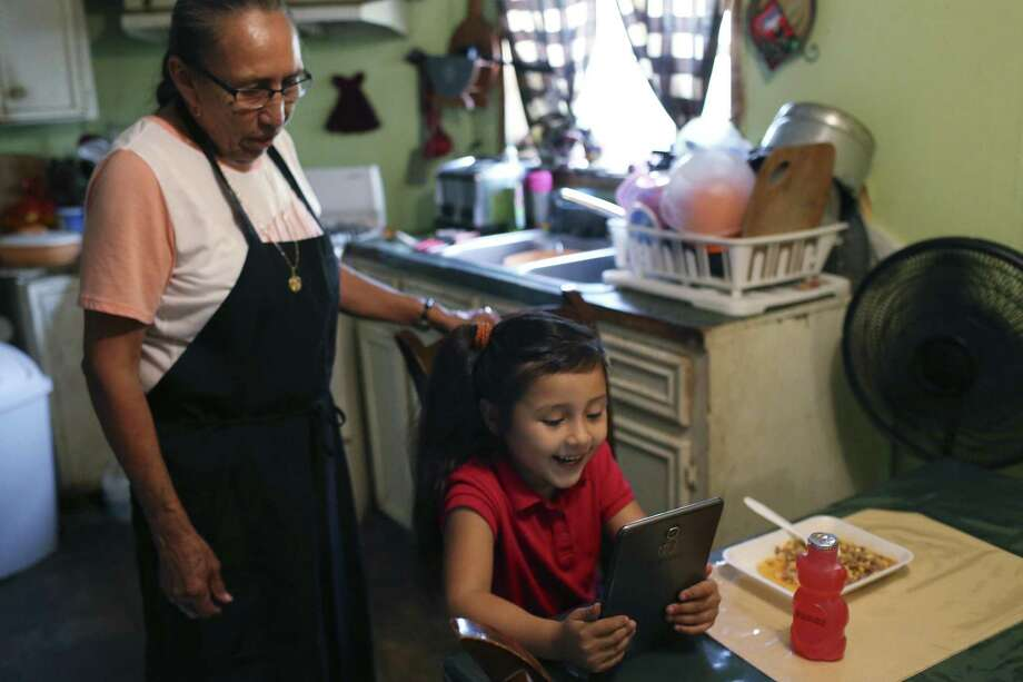 Ashlee Salazar, 5, shows her grandmother a game before she eats her dinner in the Indian Hills subdivision. Photo: JERRY LARA / San Antonio Express-News / © 2017 San Antonio Express-News