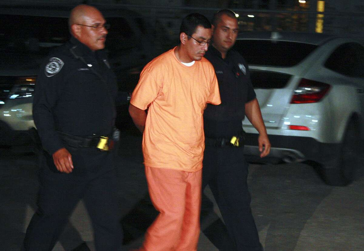 Jerry Idrogo is escorted into the Bexar County Magistrate's Office just after midnight Tuesday after being extradited from the Lucas County Corrections Center in Toledo, Ohio. Idrogo is a suspect in the shooting death of a Balcones Heights police officer.