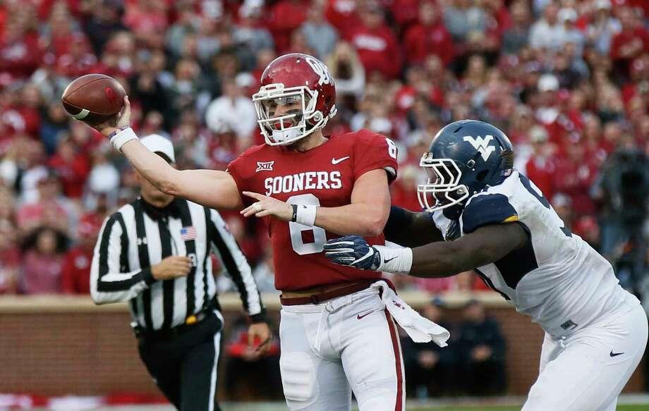 Oklahoma quarterback Baker Mayfield (6) throws under pressure from a West Virginia defender during an NCAA college football game in Norman, Okla., Saturday, Nov. 25, 2017. (AP Photo/Sue Ogrocki) Photo: Sue Ogrocki, STF / AP2017