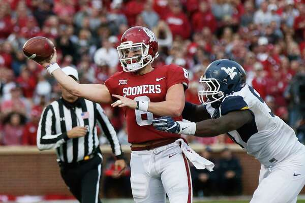 Oklahoma quarterback Baker Mayfield (6) throws under pressure from a West Virginia defender during an NCAA college football game in Norman, Okla., Saturday, Nov. 25, 2017. (AP Photo/Sue Ogrocki)