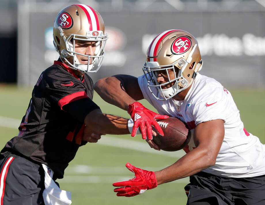 Jimmy Garoppolo (left) hands off to running back Jeremy McNichols during practice in Santa Clara. On Sunday, Garoppolo will be starting in Chicago. Photo: Tony Avelar, Special To The Chronicle