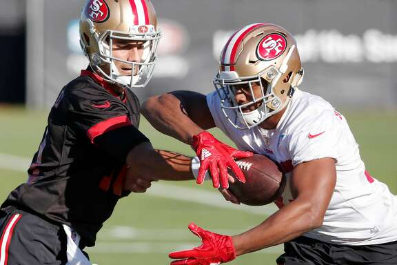 San Francisco 49ers quarterback Jimmy Garoppolo hands off to running back Jeremy McNichols during practices at the team's NFL training facility in Santa Clara, Calif., Wednesday, Nov. 29, 2017. The Niners announced Garoppolo is set to make his first start on the road this week against the Chicago Bears.