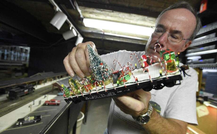 John Walther, a member of the Stamford Model Railroad Club, looks over one of his custom designed rail cars that is part of the collection of trains on display during the club's annual Holiday open house in Stamford. Photo: Matthew Brown / Hearst Connecticut Media / Stamford Advocate