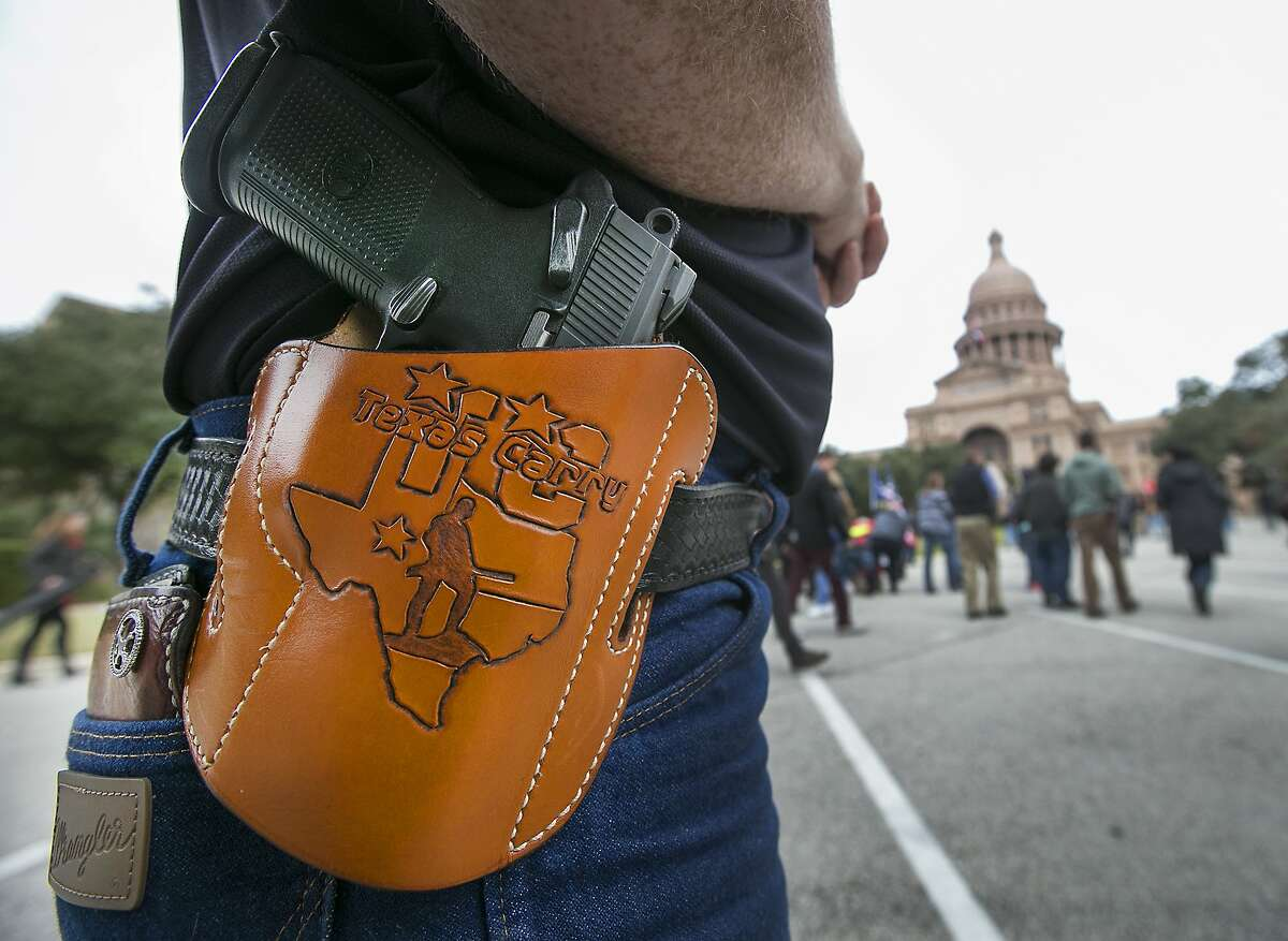 In a Friday, Jan. 1, 2016 photo, Terry Holcomb, Executive Director of Texas Carry happily displays his customized holster as he walks to the Capitol for a rally. Open Carry Texas and Texas Carry held a rally on the south steps of the Texas State Capitol in Austin to celebrate Texas becoming an open carry state. President Barack Obama defended his administration's plans to tighten the nation's gun-control restrictions without going through Congress, insisting Jan. 4 that the steps he'll announce fall within his legal authority and uphold the constitutional right to own a gun. (Ralph Barrera/Austin American-Statesman via AP) AUSTIN CHRONICLE OUT, COMMUNITY IMPACT OUT, INTERNET AND TV MUST CREDIT PHOTOGRAPHER AND STATESMAN.COM, MAGS OUT; MANDATORY CREDIT