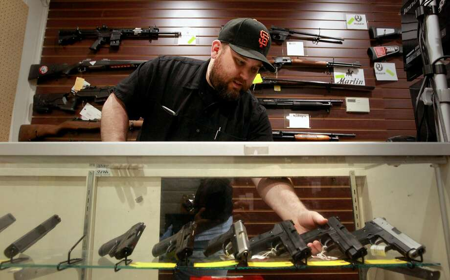 Todd Settergren of Setterarms gun shop in Walnut Creek shows a handgun that he has in a display case. Photo: Michael Macor, The Chronicle