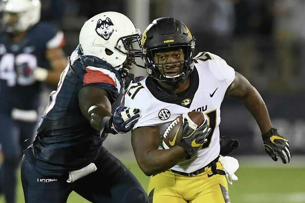 Missouri running back Ish Witter, right, is pursued by Connecticut linebacker Junior Joseph, left, during the first half of an NCAA college football game, Saturday, Oct. 28, 2017, in East Hartford, Conn. (AP Photo/Jessica Hill)